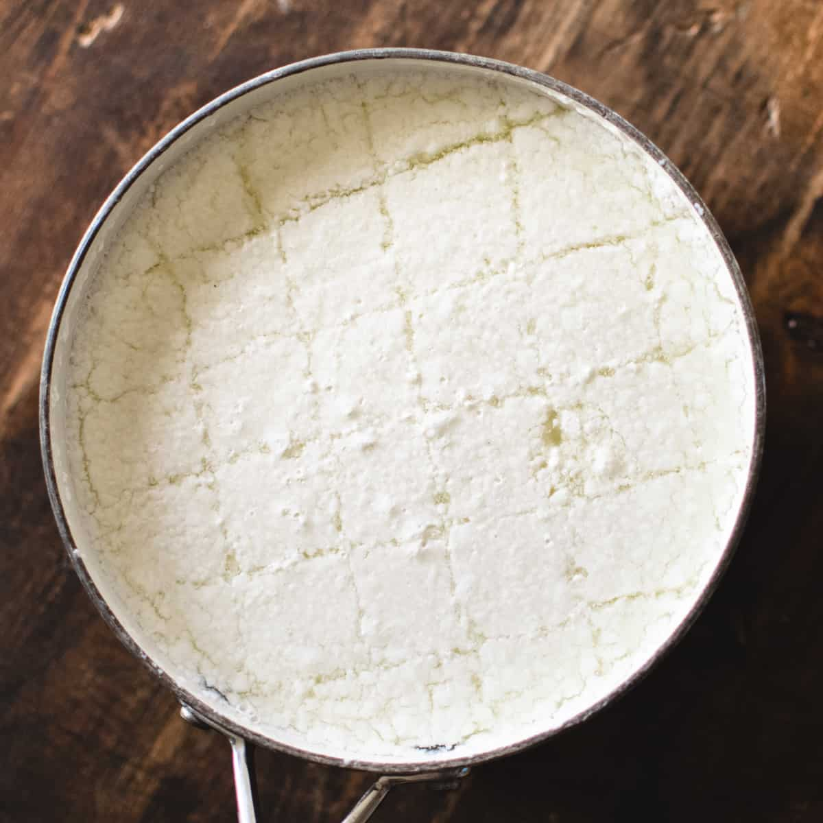 Pot of curds for mozzarella cheese cut into a grid like shape.