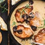 Pork chops in an iron skillet with mushrooms, sauce and herbs.