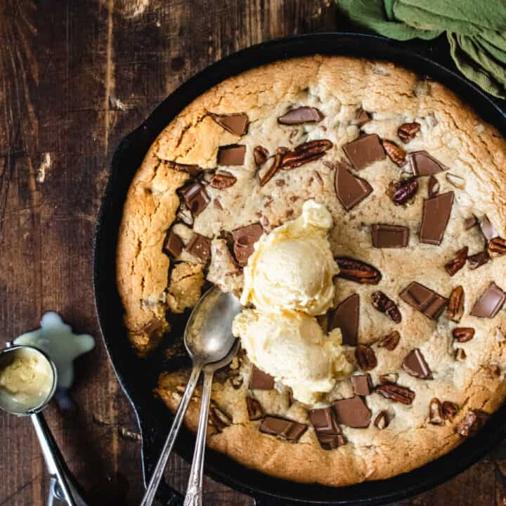 Cast iron skillet with chocolate chunks, pecans and ice cream scoops.