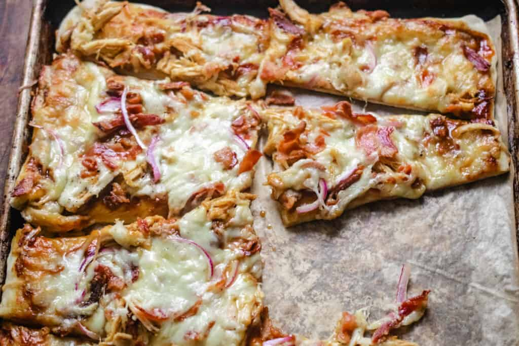 Wedge shaped slices of flatbread topped with cheese, chicken and red onion.