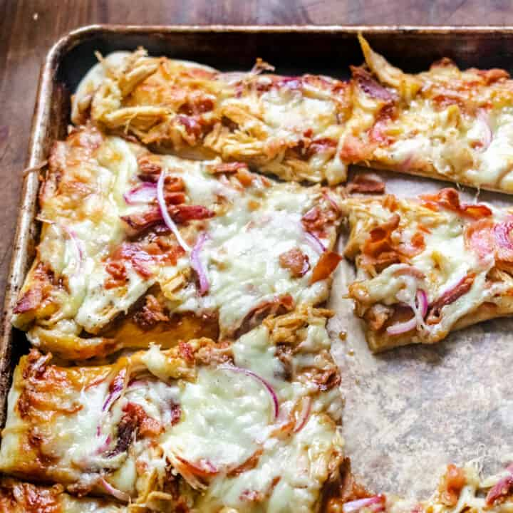 Crust topped with chicken, bacon, red onion and melted cheese and sliced into wedges on a baking sheet.