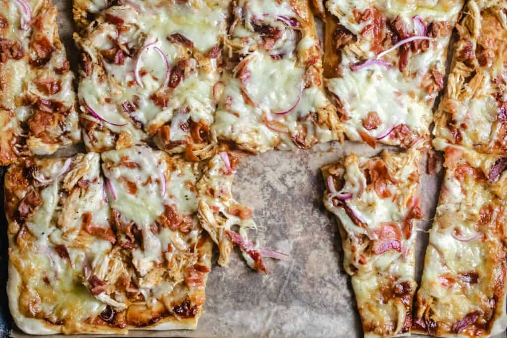 Rectangular crust with cheese, bacon, chicken and red onion with a slice removed.