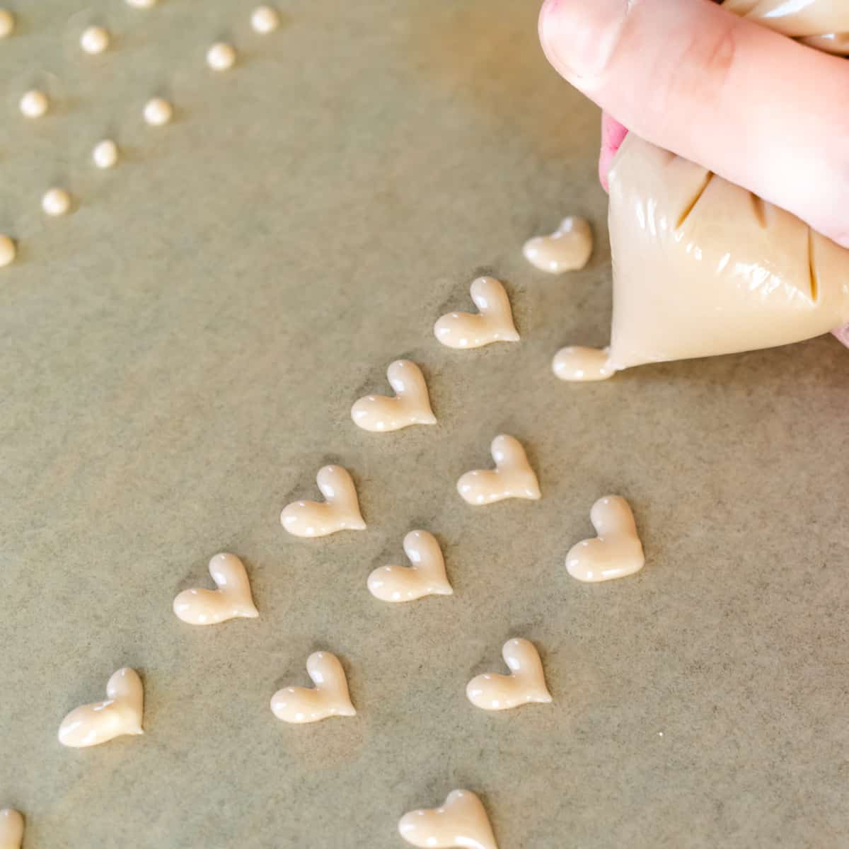 Piping heart shapes and dots onto brown parchment paper with pink sugar mixture.