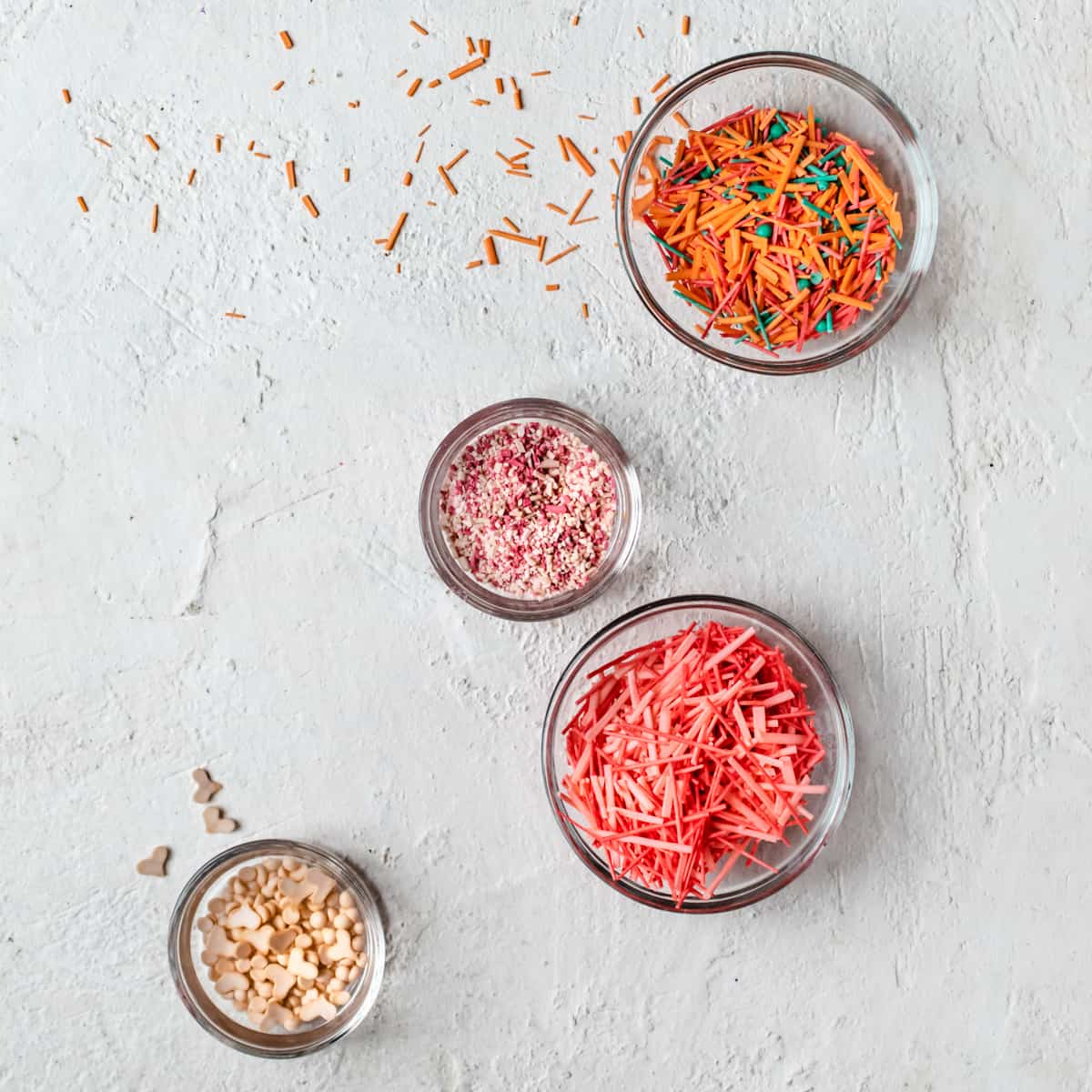 Several glass bowls filled with different shaped, sized and colored sprinkles on white background.