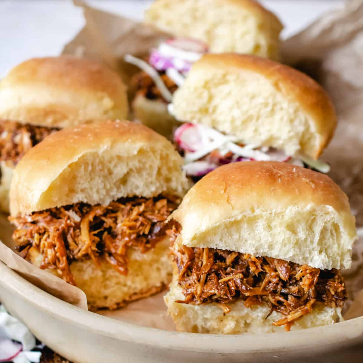 Pulled pork on slider rolls on a stone plate.