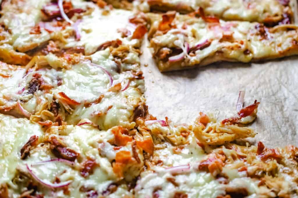 Flatbread with cheese, barbecue sauce, chicken, onion and bacon.