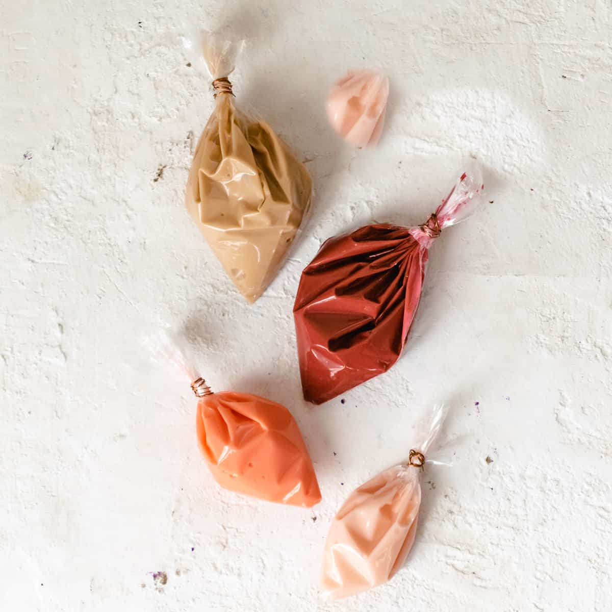 Four bags filled with the sprinkle mixture recipe in shades of pink.