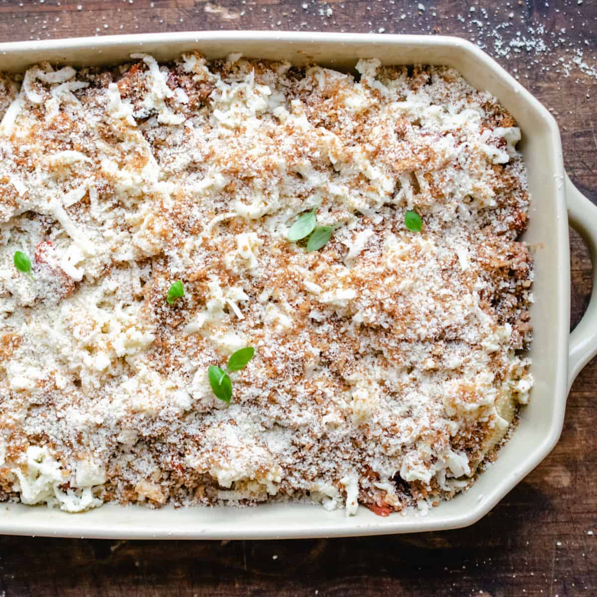 Stuffed pasta shells with mozzarella, bread crumbs and basil leaves on top.