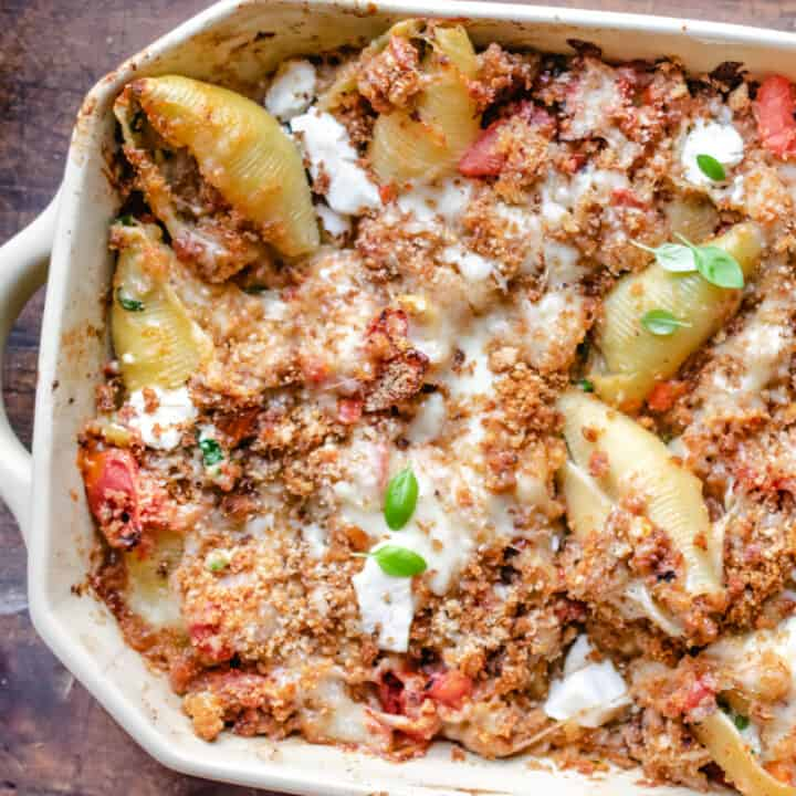 Stuffed pasta shells in a casserole dish with large serving spoon.
