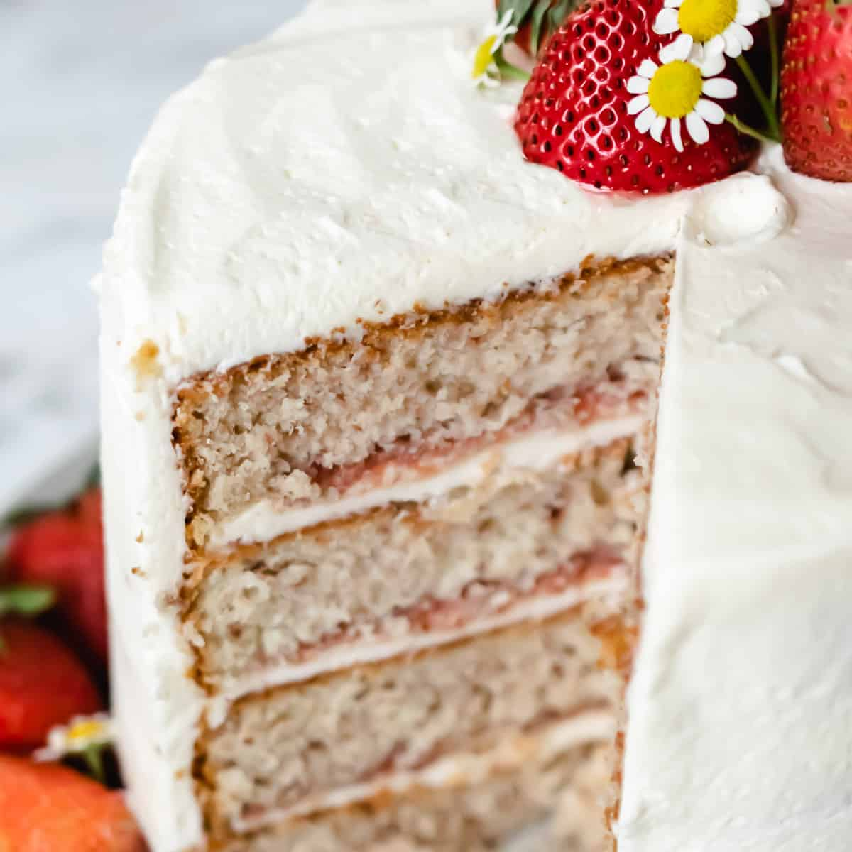 A slice taken out of a strawberry layer cake with strawberry filling.