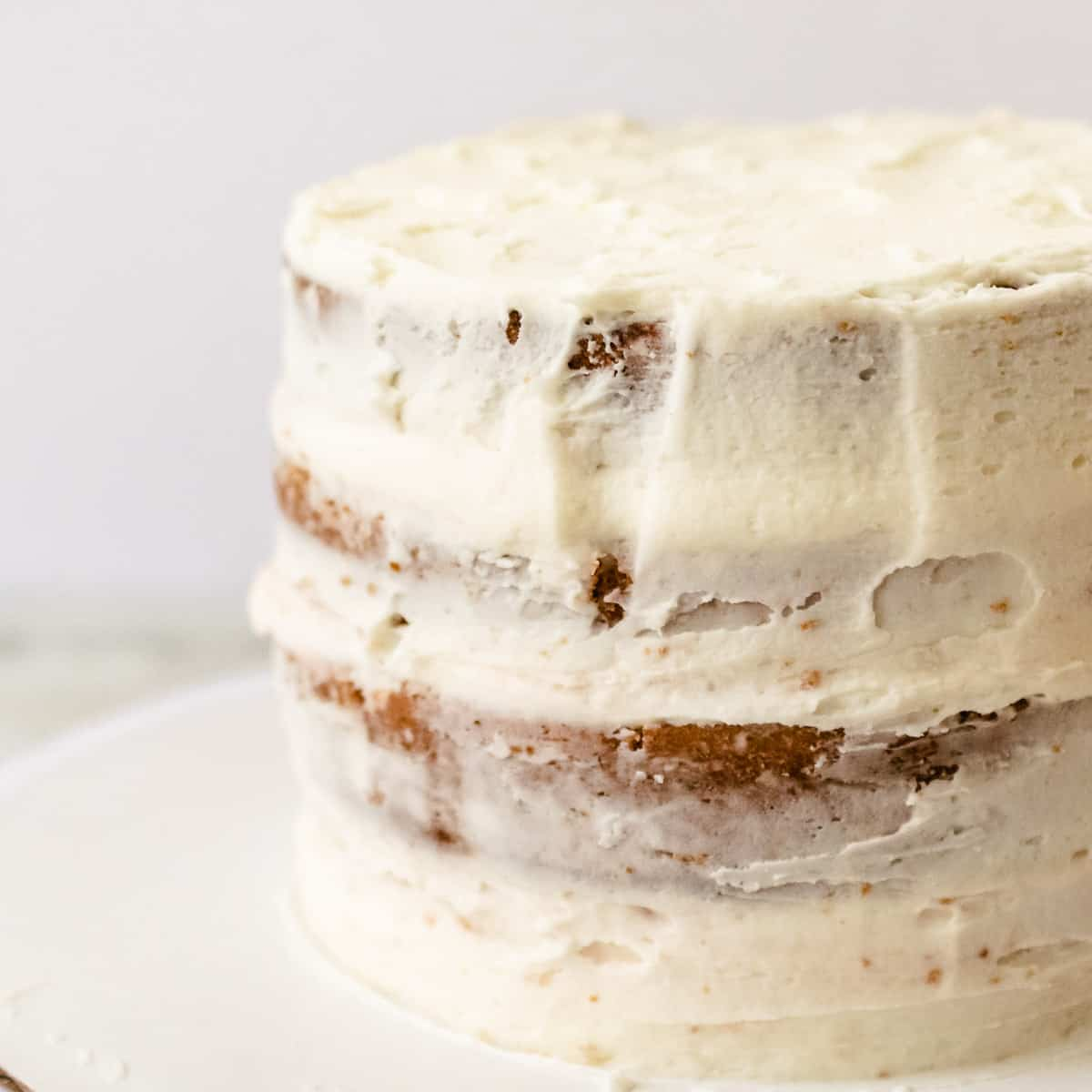 Four layers of strawberry layer cake with a white crumb coat of frosting.