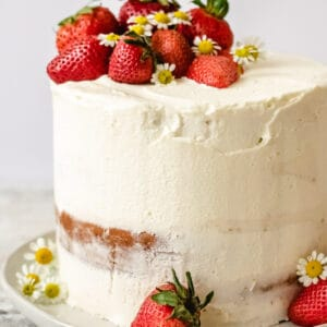 A strawberry layered cake with buttercream frosting, strawberry filling and fresh strawberries.