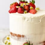Four layers of strawberry cake with white frosting, strawberry filling and fresh strawberries and daisies on top.