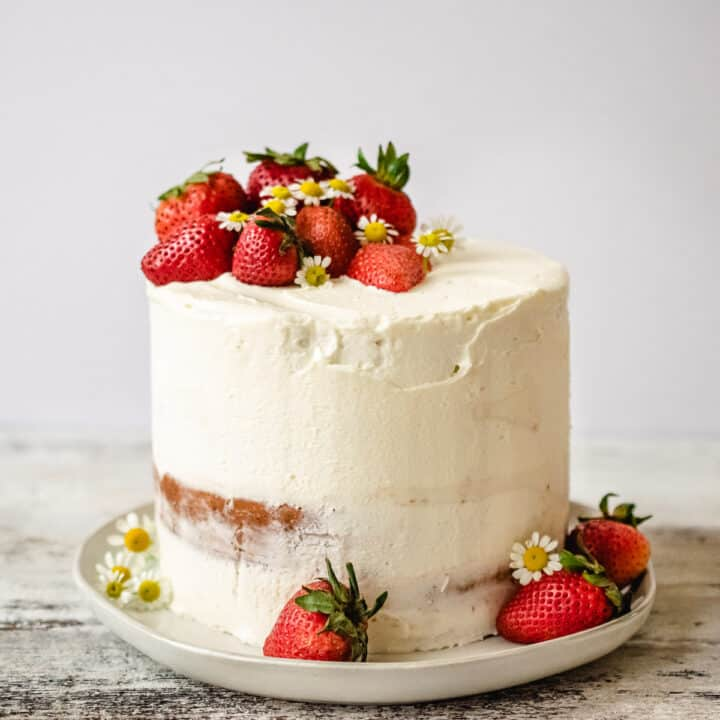 Cake with white frosting and fresh strawberries on top.
