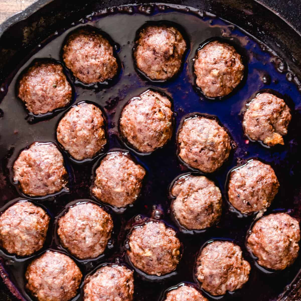 Meatballs in a skillet with a cherry sauce.
